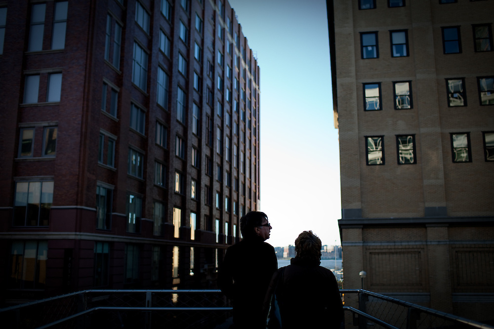 Two visitors to the High Line Park peering through buildings to view the Hudson River, New York.
