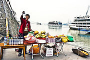 CHINA, SANDOUPING:  Female vendor selling wine, beer and fresh fruits to tourists from the cruise ships that stop at Sandouping and the Three Gorges Dam during a Yangtze River Cruise. Photo Illustration.