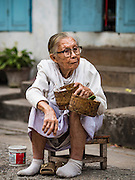 "12 MARCH 2016 - LUANG PRABANG, LAOS: A Lao woman waits to give alms to Buddhist monks during the morning tak bat in Luang Prabang. Luang Prabang was named a UNESCO World Heritage Site in 1995. The move saved the city's colonial architecture but the explosion of mass tourism has taken a toll on the city's soul. According to one recent study, a small plot of land that sold for $8,000 three years ago now goes for $120,000. Many longtime residents are selling their homes and moving to small developments around the city. The old homes are then converted to guesthouses, restaurants and spas. The city is famous for the morning ""tak bat,"" or monks' morning alms rounds. Every morning hundreds of Buddhist monks come out before dawn and walk in a silent procession through the city accepting alms from residents. Now, most of the people presenting alms to the monks are tourists, since so many Lao people have moved outside of the city center. About 50,000 people are thought to live in the Luang Prabang area, the city received more than 530,000 tourists in 2014.       PHOTO BY JACK KURTZ"