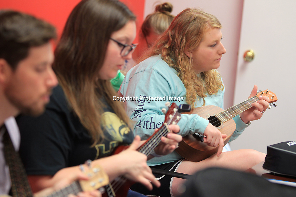 Cassandra Robertson, of Fulton, reads the sheet music as she practices the Ukulele with the others in her group.