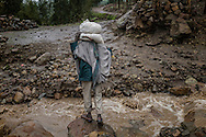 Farmer prepares to jump across rain swollen stream that dries out completely during dry times but usually heavy rains in the Northern Ethiopian Highlands this year sometimes make the long walk back to remote villages nearly impassable.  Outside of bigger towns the only way to get some place is to walk.  Northern Ethiopian Highlands