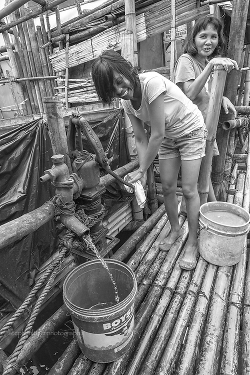 Everyday life in a fishing village community with nearly everything built from bamboo on top of stilts on the edge of a lake. Lake water is pumped up from below into buckets to be used for bathing, cooking and laundry