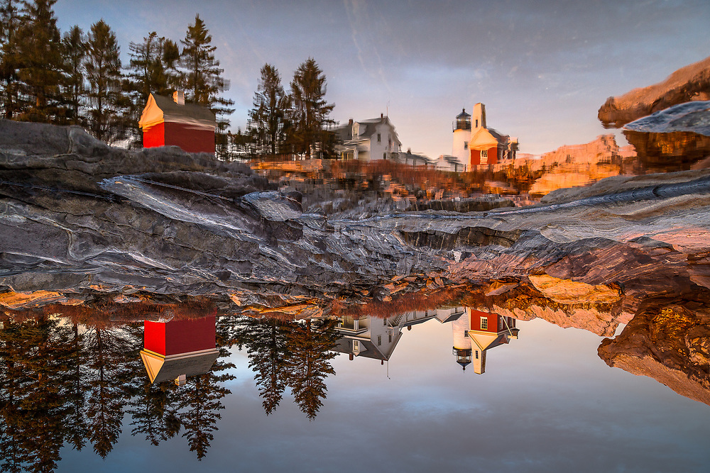 Golden light from sunset shines on Pemaquid Point Lighthouse. Look closely and you'll see that the reflection isn't as it first appears.