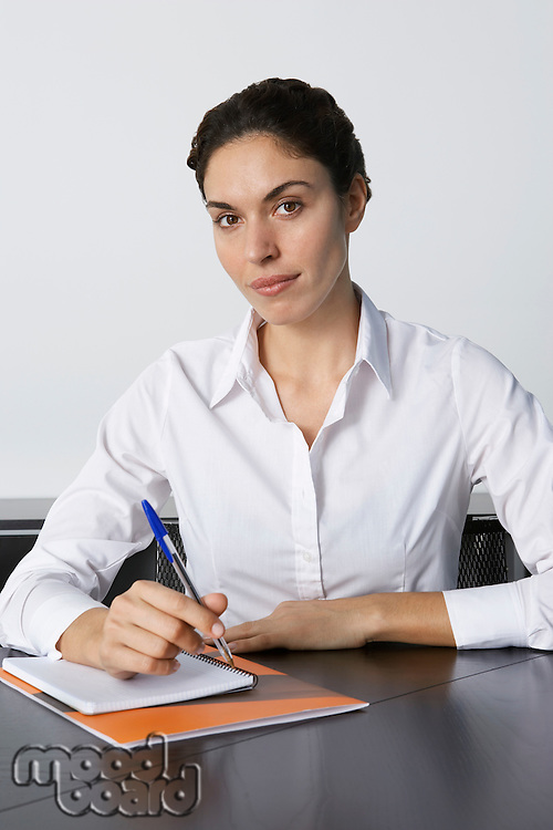 Business woman writing at desk in office portrait