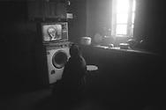 Senora Serafina do Roquino, viendo la misa en una televison situada encima de la lavadora