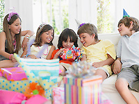 Children (7-12) sitting on sofa watching one open birthday present