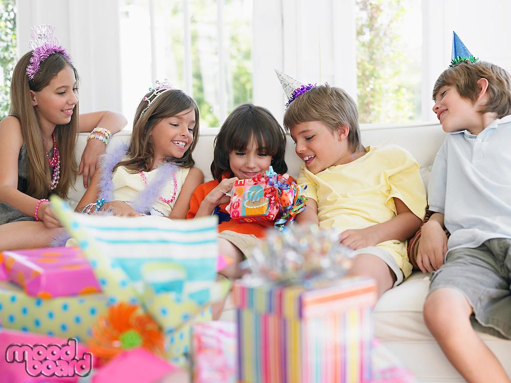 Children (7-12) sitting on sofa watching one open birthday present