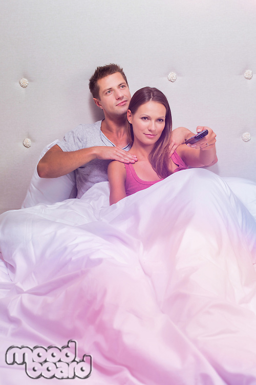 Portrait of attractive couple watching tv in bed