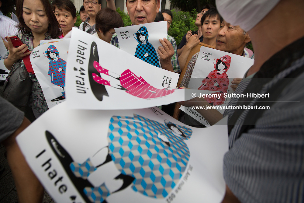 "The street art designer known as '281 Anti Nuke' gives out his anti-nuclear illustrations posters to Japanese public, as the protest against the Japanese government's nuclear energy policies, demanding a change of energy policy, and also voice their opposition to the restarting of nuclear plants which are currently offline for safety checks, in the streets near the Japanese Prime Minister's official residence, in Tokyo, Japan, on Friday 6th July 2012. The Friday evening demonstrations,  which have been ongoing since March this year, and which in the past four weeks have grown considerably in size, are being talked of as the ""Hydrangea Revolution"" by protestors, as it is hydrangea flower season in Japan."