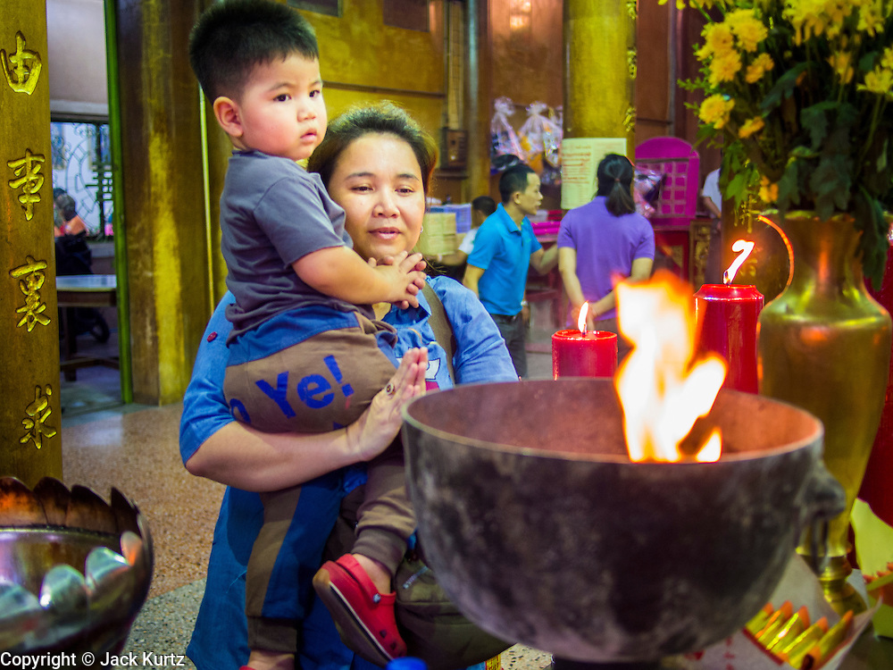 06 FEBRUARY 2014 - HAT YAI, SONGKHLA, THAILAND: A woman and her son offer New Year's prayers in the Tong Sia Siang Tueng temple in Hat Yai. Hat Yai was originally settled by Chinese immigrants and still has a large ethnic Chinese population. Chinese holidays, especially Lunar New Year (Tet) and the Vegetarian Festival are important citywide holidays.     PHOTO BY JACK KURTZ