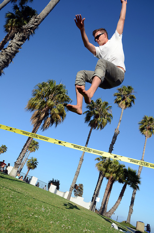 Young man slacklining at Cabrillo Park in Santa Barbara, CA.