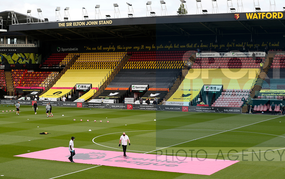 Two men in gloves and masks lay out the Premier League logo during the Premier League match at Vicarage Road, Watford. Picture date: 20th June 2020. Picture credit should read: Darren Staples/Sportimage