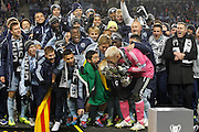 Sporting Kansas City players watch as goalkeeper Jimmy Nielsen kisses the MLS Cup as they celebrate their 2-1 win over Real Salt Lake in the MLS Cup final soccer match in Kansas City, Kan., Saturday, Dec. 7, 2013. (AP Photo/Colin E. Braley)