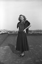 1950's portrait of a woman in a dress and fur on a rooftop of an apartment building in the Bronx