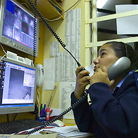 Radio controller Candice James takes an emergeancy call about an intruder in Hout Bay, Cape Town, South Africa, and sends neighbourhood watch founder Rod Pond.... The work of the CPF and neighbourhood watch have seen the crime rate in Hout Bay drop 63%, but relations between the shanty town of Imizamo Yethu and Hout Bay are tense.  photo  Leonie Marinovich