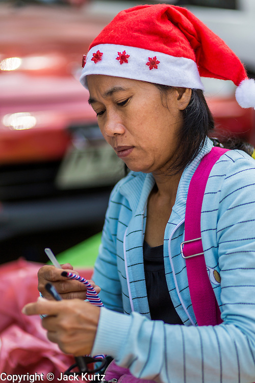 24 DECEMBER 2013 - BANGKOK, THAILAND: A woman wearing a Santa hat makes souvenirs for anti-government protestors the Thai-Japan Stadium in Bangkok. Hundreds of anti-government protestors are camped out around the Thai-Japan Stadium in Bangkok, where political parties are supposed to register for the election on February 2. As of Dec 24, nine of the more than 30 parties were able to register. Protestors hope to prevent the election. The action is a part of the ongoing protests in Bangkok that have caused the dissolution of the elected government.      PHOTO BY JACK KURTZ