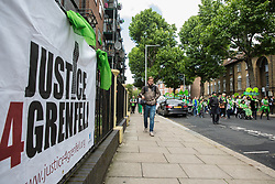 London, UK. 14 June, 2019. Family members walk in silence to lay tributes at the foot of the Grenfell Tower following a memorial service at St Helen's Church to mark the second anniversary of the Grenfell Tower fire on 14th June 2017 in which 72 people died and over 70 were injured.