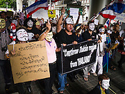 "02 JUNE 2013 - BANGKOK, THAILAND: A legless man (lower right) leads a protest march through the Bangkok skywalk system. About 300 people wearing the Guy Fawkes mask popularized by the movie ""V for Vendetta"" and Anonymous, the hackers' group, marched through central Bangkok Sunday demanding the resignation of Prime Minister Yingluck Shinawatra. They claim that Yingluck is acting as a puppet for her brother, former Prime Minister Thaksin Shinawatra, who was deposed by a military coup in 2006 and now lives in exile in Dubai.      PHOTO BY JACK KURTZ"