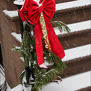 Snowing Christmas bow and bell decorations on front stair to brownstone building in Greenwich Village.