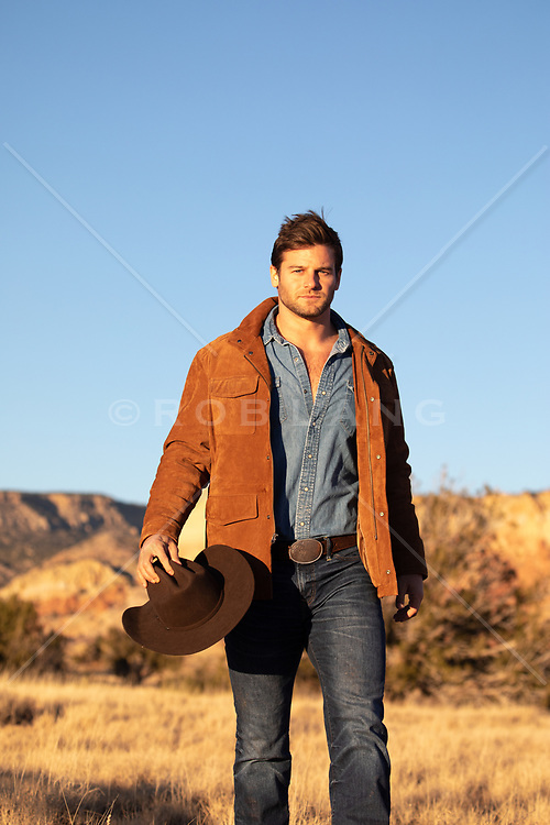 rugged cowboy outdoors at sunset on a ranch