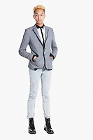 Portrait of a teenage boy standing in smart casuals over gray background