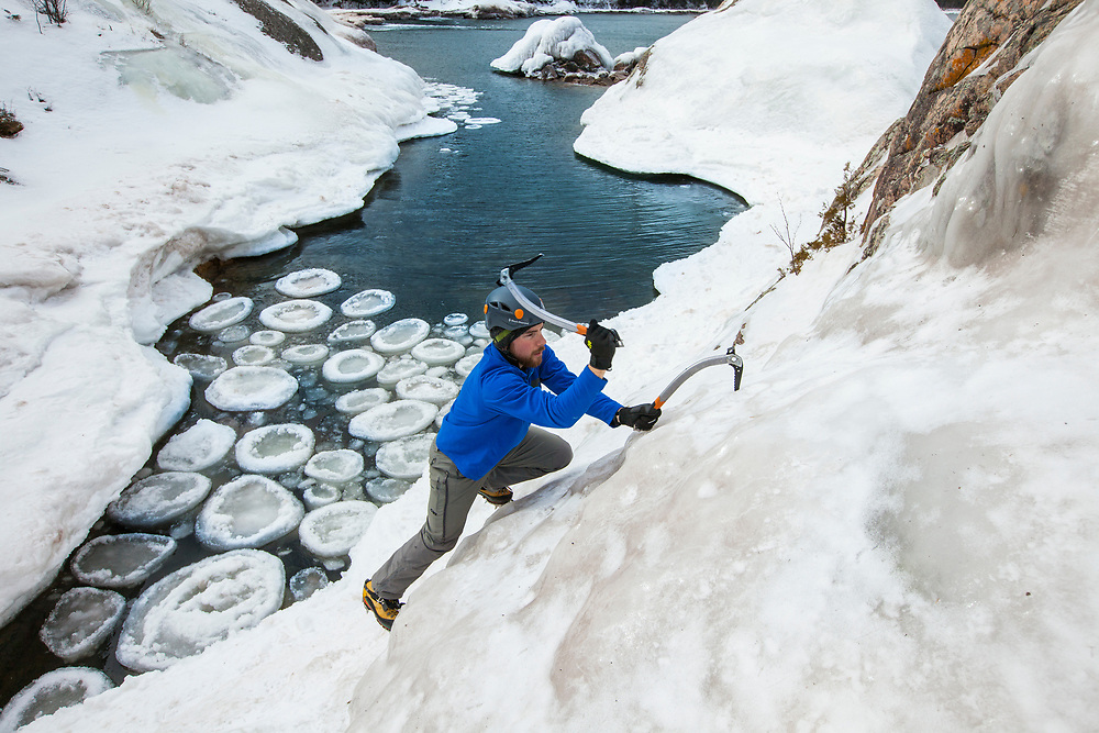 Ice bouldering with ice climbing tools and crampons on the ice covered rocky shoreline of Lake Superior near Marquette and Munising, Michigan.