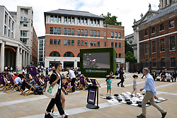 Tour de France being shown on a big screen in Paternoster Square near St Paul's cathedral, City of London UK July 2019