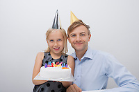 Portrait of happy man with daughter holding birthday cake against gray background