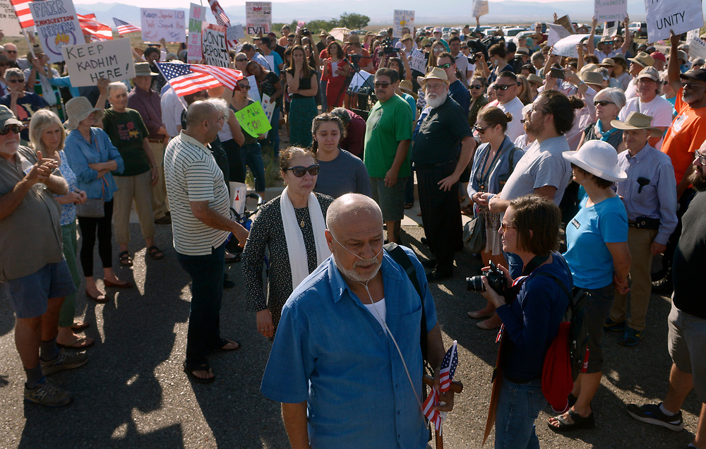 gbs062617e/ASEC -- Kadhim Al-bumohammed, center, followed by his wife, Reeham Majedd, and daughter, Courtney Al-bumohammed, walk through hundreds of supporters outside the U.S. Immigration and Customs Enforcement Field Office on Monday, June 26, 2017. Al-bumohammed was scheduled to met to plead for ICE not to deport him and separate him from his wife and children. He was turned away from the Filed Office after being informed all appointments were cancelled for the day.(Greg Sorber/Albuquerque Journal)