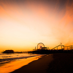 Photo of Santa Monica Pier sunset over the Pacific Ocean in Southern California. Santa Monica Pier is a landmark that has an amusement park with a ferris wheel, roller coaster, restaurants, and other attractions.