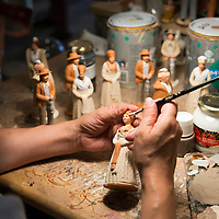 An artisian paints ceramic figurines at Atelier Arterra, a workshop and store located in the Panier neighborhood of Marseille, France, that sells traditional painted ceramic figurines known as santons.