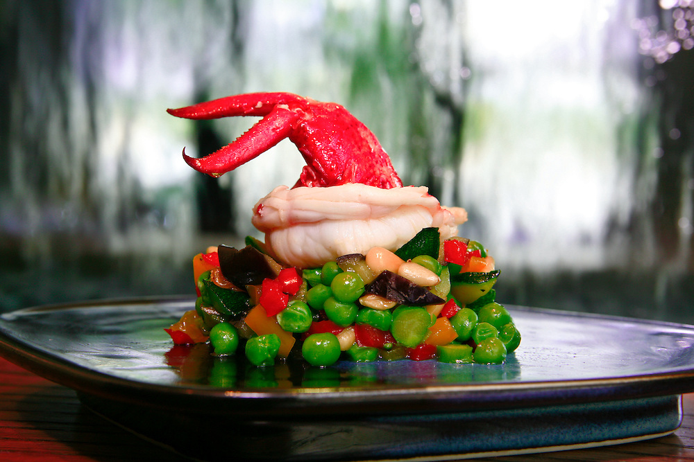 A lobster tail waves over a pea salad D'Acqua.