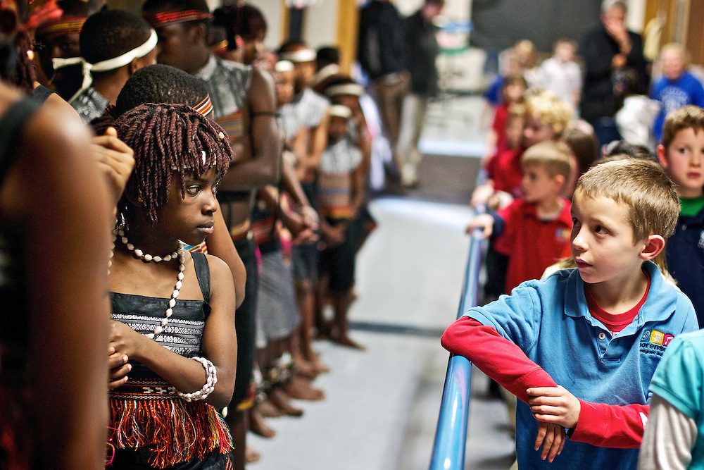Joe DuCoeur, 7, and a member of the Asante children's choir share a passing look before the group's performance.