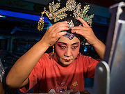 "30 JUNE 2016 - BANGKOK, THAILAND: A performer puts on her costume before a Chinese opera performance at Chiao Eng Piao Shrine in Bangkok. Chinese opera was once very popular in Thailand, where it is called ""Ngiew."" It is usually performed in the Teochew language. Millions of Chinese emigrated to Thailand (then Siam) in the 18th and 19th centuries and brought their culture with them. Recently the popularity of ngiew has faded as people turn to performances of opera on DVD or movies. There are about 30 Chinese opera troupes left in Bangkok and its environs. They are especially busy during Chinese New Year and Chinese holidays when they travel from Chinese temple to Chinese temple performing on stages they put up in streets near the temple, sometimes sleeping on hammocks they sling under their stage.       PHOTO BY JACK KURTZ"