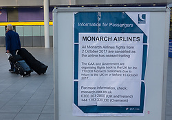 © Licensed to London News Pictures. 02/10/2017. Crawley, UK. A passenger walks past a poster at Gatwick Airport announcing that Monarch Airlines has ceased trading. The government has announced that it will start the country's biggest ever peacetime repatriation to fly about 110,000 stranded passengers home. Photo credit: Peter Macdiarmid/LNP