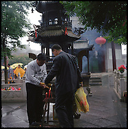 Two men light incense for an offering at the Temple.  Many incense offerings are made here in Wu Tai Xian.