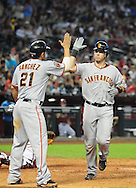 Apr. 17 2011; Phoenix, AZ, USA; San Francisco Giants batter Buster Posey (28) is congratulated by teammate Freddy Sanchez (21) after hitting a two run home run during the sixth inning against the Arizona Diamondbacks at Chase Field. Mandatory Credit: Jennifer Stewart-US PRESSWIRE..