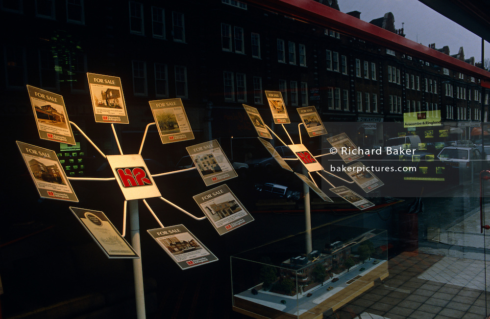 Housing properties are displayed in a South London estate agent's window with surrounding steet and houses reflected in window