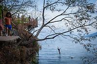 Lake Atitlan, Guatemala.  A visitor jumps off a platform near San Marcos La Laguna