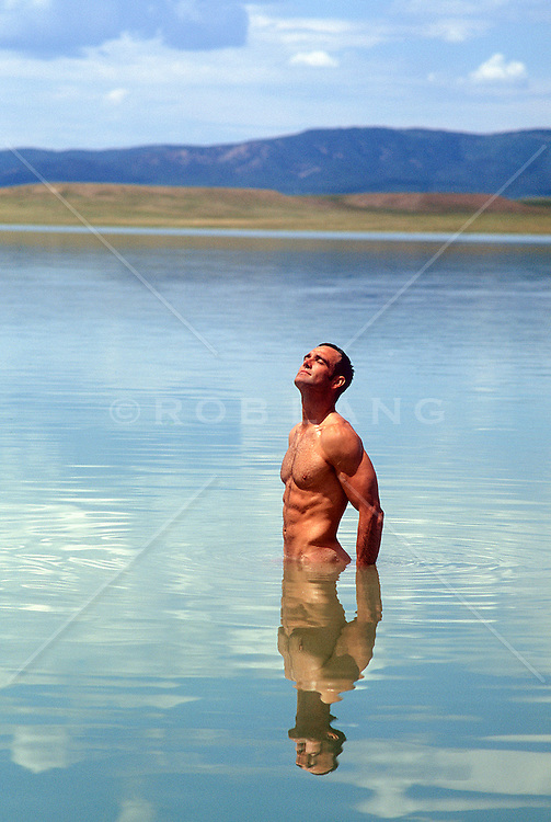 man alone in a beautiful lake soaking up the sun