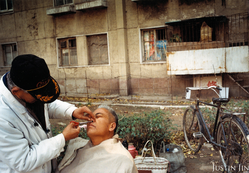 A barber cuts the nostril hairs of a client in Shenyang City, in China's northeastern rustbelt. .Millions of workers have been laid-off as China restructures its economy, making way for nimble manufacturing bases down south. Thousands of unemployed workers from Shenyang have fled to Europe as clandestine immigrants.