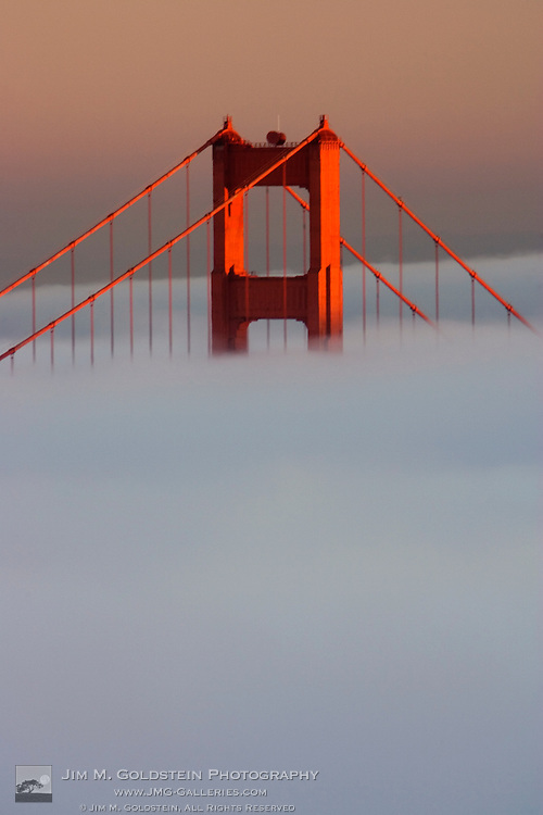 Fog rolls through the San Francisco bay covering the Golden Gate Bridge. Pictured is the top of the Golden Gate Bridge's south tower sticking out of the fog at sunset.