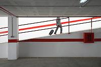 Businessman walking up ramp in parking garage with luggage