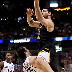 Mar 19, 2011; Tampa, FL, USA; West Virginia Mountaineers forward Deniz Kilicli (13) draws a charging foul after colliding with Kentucky Wildcats forward Josh Harrellson (55) during the first half of the third round of the 2011 NCAA men's basketball tournament at the St. Pete Times Forum.  Mandatory Credit: Derick E. Hingle