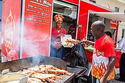 "Eustac Weekes grills stuffed lobster on the grill for patrons with Kathlyn Reynold.  ""Alvin's Cultural Workshop"" Cultural Fair honoring Mr. Alvin Turnbull.  Emancipation Garden.  St. Thomas, VI.  29 April 2015.  © Aisha-Zakiya Boyd"