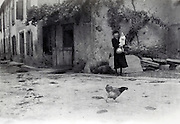 woman holing a young child with a running chicken in foreground rural France