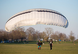 © Licensed to London News Pictures; 26/03/2020; Bristol, UK. Coronavirus Pandemic 2020; people fly a paraglider on Bristol Downs during the UK wide lockdown declared by the prime minister on Monday evening, with the biggest restrictions on freedom of movement ever imposed in the UK. People are told to stay at home except for essential work that cannot be done at home, shopping for food, medical appointments and taking exercise once a day all while maintaining social distance. Photo credit: Simon Chapman/LNP.