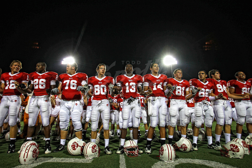 Members of the Katy Tiger football team stand for the school song, following the week 0 matchup between the North Shore High School Mustangs and the Katy High School Tigers at Rhodes Stadium in Katy, Texas. The Tigers won the game 7-9. (Todd Spoth/HCN)