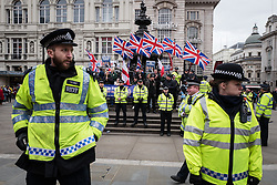 © Licensed to London News Pictures. 19/03/2016. London, UK. Police stand guard at a small Britain First counter-demonstration in Piccadilly Circus. Thousands march through central London on UN anti-racism day to demand that the British government accept a greater share of refugees seeking asylum in Europe. Photo credit : Rob Pinney/LNP