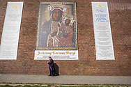 A priest passes a banner, showing a picture of the Black Madonna, during the celebration of the assumption of Mary in August, Poland in 2018.